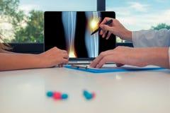 显示腿的X-射线充满痛苦的医生在膝盖和脚腕在膝上型计算机对妇女患者 在书桌上的药片 免版税库存图片