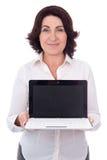 显示膝上型计算机与的美丽的成熟的商业妇女画象  图库摄影