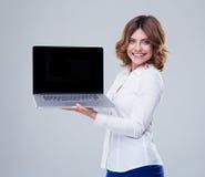 显示膝上型计算机屏幕的愉快的女实业家 图库摄影