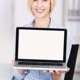显示膝上型计算机的女实业家在办公室 库存图片