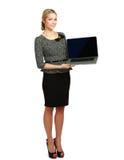 显示膝上型计算机的年轻美丽的妇女 免版税库存照片