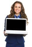 显示膝上型计算机黑屏的微笑的女商人 免版税库存照片