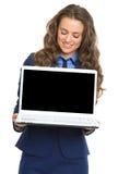 显示膝上型计算机黑屏的愉快的女商人 库存照片