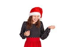 显示舌头和看在笑下的美妙的快乐的妇女 情感女孩在圣诞老人在白色backgr隔绝的圣诞节帽子 库存照片