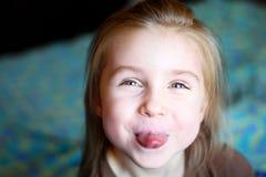 显示舌头的可爱的小女孩 免版税图库摄影