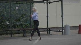 显示艺术性的技能典雅的移动和跳舞天分的白肤金发的雇员拉丁美州的舞蹈公开,当等待公共汽车的她-时 影视素材