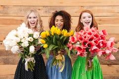 显示花的花束三名妇女在照相机 免版税库存照片