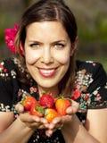 显示草莓的美丽的女孩 免版税图库摄影