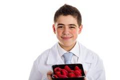 显示草莓的医疗白色外套的孩子 免版税库存图片