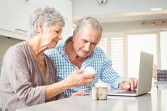 显示药片的资深妇女对有膝上型计算机的丈夫 免版税库存图片