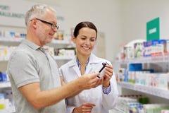 显示药物的药剂师对老人在药房 免版税库存图片
