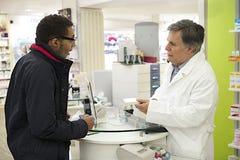 显示药物的资深药剂师在药房对顾客 库存图片