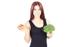 显示葡萄柚和硬花甘蓝的微笑的秀丽妇女 妇女坐饮食 素食主义者食物 库存图片
