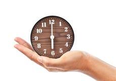 显示葡萄酒棕色时钟的女性手 免版税库存图片
