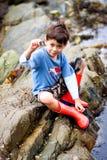 显示蜗牛的男孩rockpool 免版税库存图片