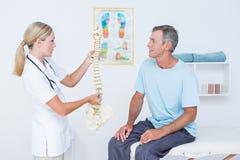 显示解剖脊椎的医生对她的患者 免版税库存照片