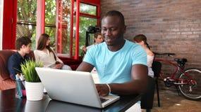 显示计算机的一位愉快的非裔美国人的企业家的画象在办公室 免版税库存图片