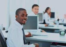 显示计算机膝上型计算机的一位愉快的非裔美国人的企业家的画象在办公室 图库摄影