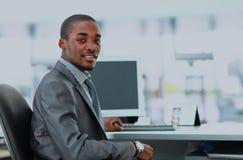 显示计算机膝上型计算机的一位愉快的非裔美国人的企业家的画象在办公室 免版税库存图片