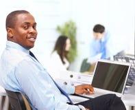 显示计算机膝上型计算机的非裔美国人的企业家在办公室 免版税库存图片