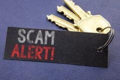 显示诈欺戒备的手写的文本 企业在便条纸写的欺骗警告的概念文字附有钥匙,黑b 免版税库存照片