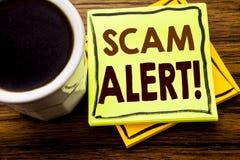 显示诈欺戒备的手写的文本 在木木背景的稠粘的便条纸写的欺骗警告的企业概念 免版税图库摄影