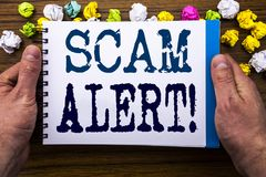 显示诈欺戒备的文字文本 在笔记薄在木木背景的笔记本书写的欺骗警告的企业概念 图库摄影