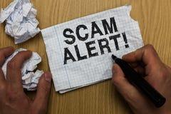 显示诈欺戒备的文字笔记 陈列企业的照片警告某人关于计划或欺骗通知举行ma的任何异常的人 免版税库存照片
