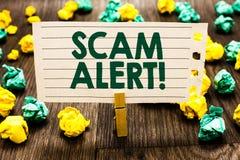 显示诈欺戒备的文本标志 概念性照片警告某人关于计划或欺骗通知举行noteboo的任何异常的晒衣夹 免版税库存图片
