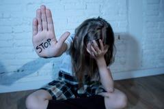 显示词中止的哀伤的女孩写在她的手 暴力、恶习和胁迫的概念 库存图片