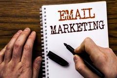 显示词电子邮件行销的手写的文本 在片剂膝上型计算机写的网上网促进的企业概念,木backgrou 库存图片