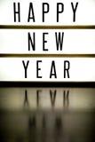 显示词组新年快乐的委员会的光 库存照片