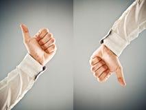 显示赞许和拇指下来标志的商人 免版税库存照片
