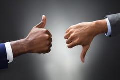显示赞许和拇指的手下来签字 免版税库存图片