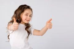 显示赞许姿态的小女孩隔绝在白色背景 免版税库存图片