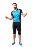 显示赞许手势的蓝色球衣的愉快的成功的体育骑自行车者 免版税库存图片