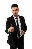 显示赞许标志的英俊的年轻商人 免版税图库摄影