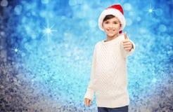 显示赞许的圣诞老人帽子的微笑的愉快的男孩 库存照片