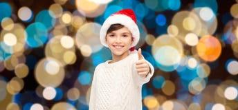 显示赞许的圣诞老人帽子的男孩在圣诞节 免版税库存图片