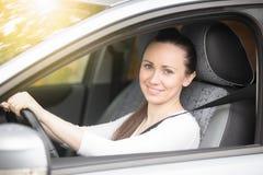 显示赞许的微笑的夫人司机画象  免版税库存图片