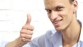 显示赞许的愉快的凉快的微笑的新鲜的人 库存照片