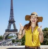 显示赞许的愉快的妇女反对埃佛尔铁塔在巴黎 免版税库存图片