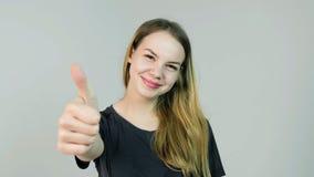 显示赞许的愉快的微笑的美丽的少妇在白色背景打手势 免版税库存图片