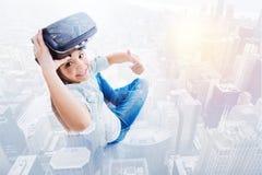 显示赞许的逗人喜爱的女孩,当去除VR耳机时 免版税图库摄影
