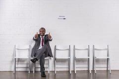 显示赞许的非裔美国人的商人,当等待时 免版税库存照片