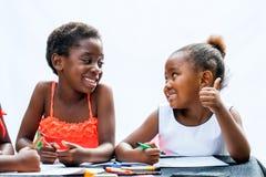 显示赞许的非洲女孩对朋友在书桌 库存图片