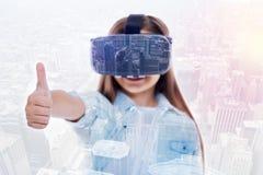 显示赞许的VR耳机的逗人喜爱的小女孩 库存照片