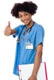 显示赞许符号的愉快的夫人医生 免版税库存照片
