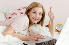 显示赞许美丽的柔和的甜少妇画象在与膝上型计算机看照相机的个人计算机计算机的床 免版税库存图片