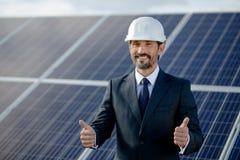 显示赞许,在他后的太阳电池板的商人 图库摄影